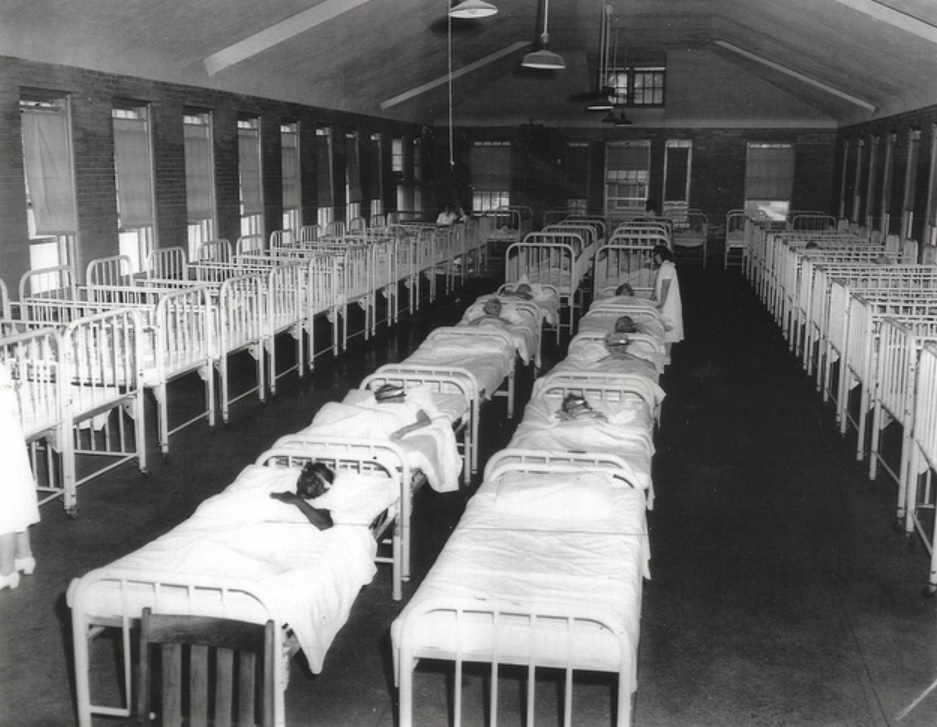"Chicago Times, 1958. Inscription on back reads: ""Crowded female infirmary at Manteno. All crib-like beds are occupied. Faces are blocked out to prevent identification. Women standing are attendants&quot"