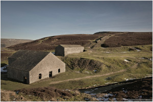 The smelt mill (foreground), peat drying house (background) and remains of the flue heading up the hillside at Grinton workings.
