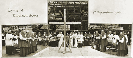 """Archbishop Scanlan laying the foundation stone before the 'entire hierarchy of Scotland', 8 September 1964. In central group, immediately to the left of cross: Professor James McShane (in white) and Rector Connolly. In left hand group, front row: Archbishop Grey (left) with Bishop McGhee of Galloway behind. In right hand group, front row, from left: Bishop Ward, Bishop Hart of Dunkeld, Bishop Black of Paisley, in right hand group, at centre of back row: Father James McMahon."""