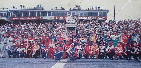 All 37 drivers from the starting grid pose before the final NASCAR Holly Farms 400 race at North Wilkesboro Speedway, September 1996. Race winner Gordon is kneeling in front on left, Earnhardt is intimidating in white, just behind and to the right.