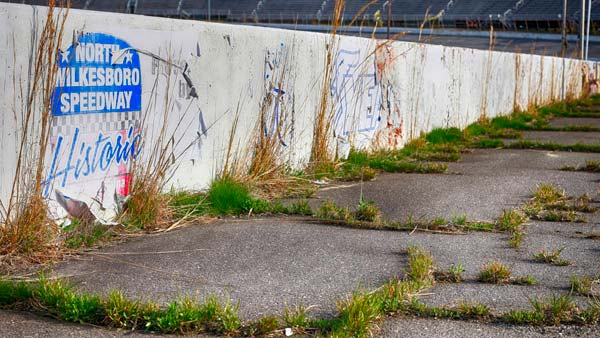 Grass grows on what's left of the Historic North Wilkesboro Speedway.