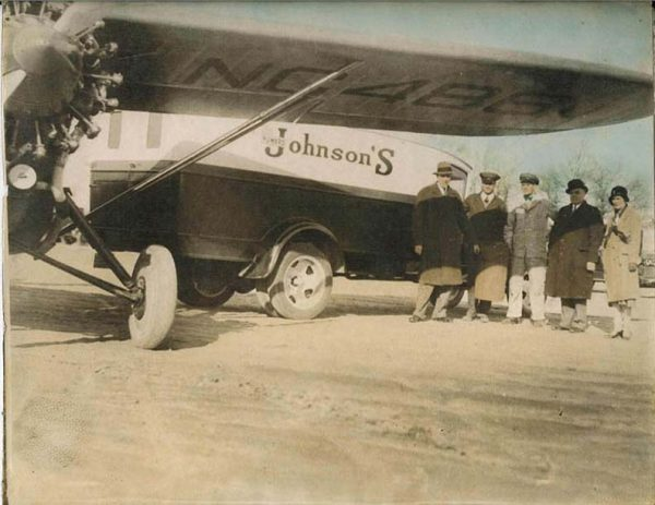 Howard D. Johnson stands (second from right) with one of his delivery trucks and planes.